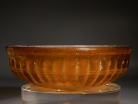 Early Roman golden-amber glass ribbed bowl.