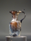 Roman amber glass juglet with trefoil mouth and ribbed body.