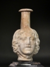 Roman molded opaque white glass Medusa Janus head flask.